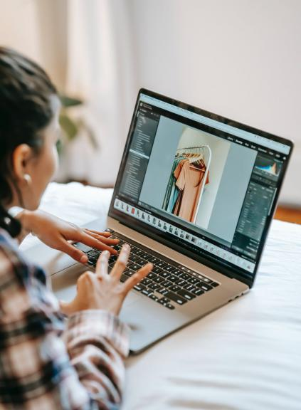 over the shoulder view of person using laptop with image of dresses on rack